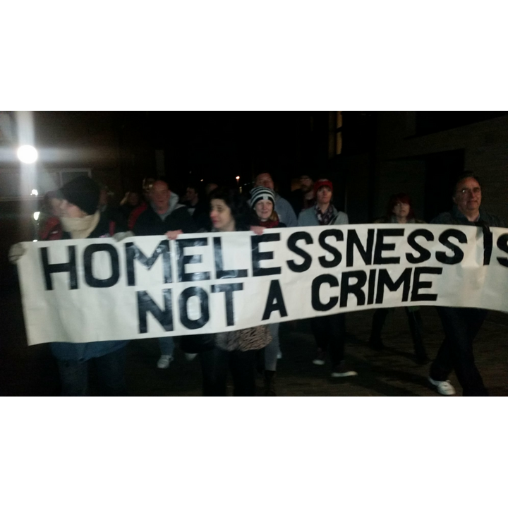 Homelessness is not a crime banner and people marching